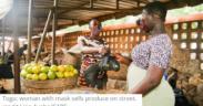 Togo woman with mask sells produce on street, credit Lina AyabaCARE