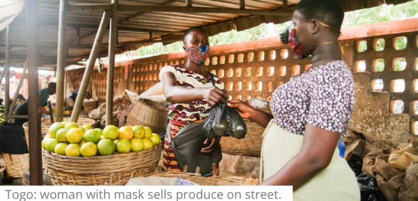 Togo woman with mask sells produce on street, credit Lina AyabaCARE